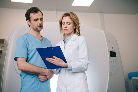 Two radiologists standing looking at diagnosis on clipboard while standing near computed tomography scanner Zdjęcie Seryjne