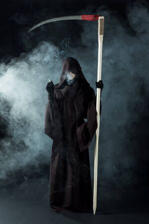 full length view of woman in death costume holding scythe and smoking cigarette on black