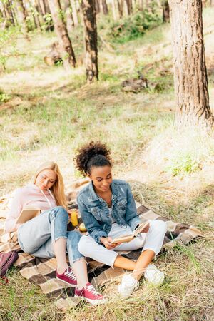 two multiethnic friends sitting on plaid blanket and reading books