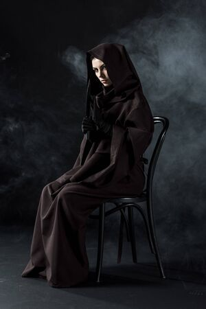 Woman in death costume holding knife and sitting on chair on black background