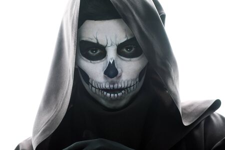 Front view of woman with skull makeup looking at camera isolated on white background