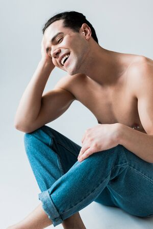 happy and shirtless man sitting in blue jeans on white Banco de Imagens