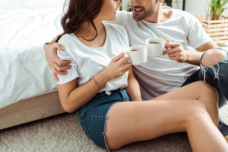 cropped view of man and cheerful woman holding cups of coffee in bedroom