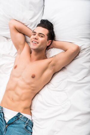 overhead view of happy shirtless man smiling while lying on bed