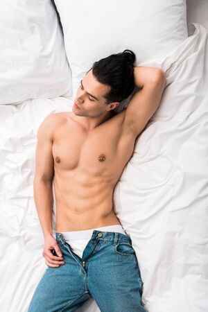 overhead view of handsome and sexy man lying on bed