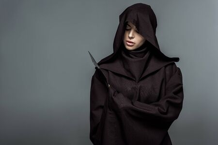 Woman in death costume holding knife isolated on grey background Imagens - 125074456