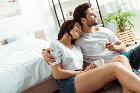 handsome man sitting with cheerful girl and holding cup in bedroom