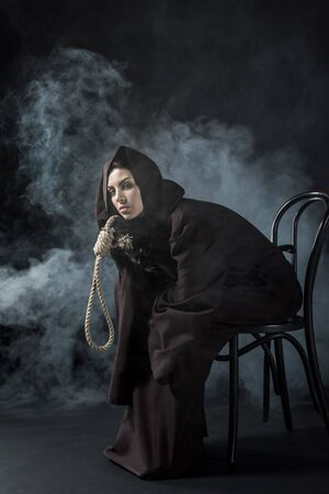 Woman in death costume sitting on chair and holding hanging noose on black background 写真素材