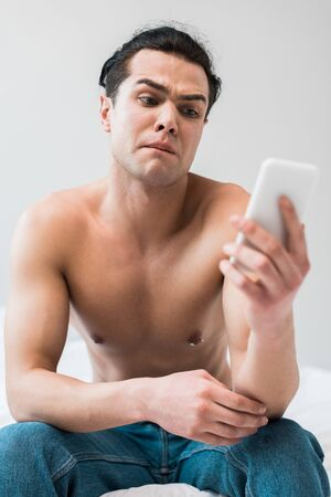 selective focus of shirtless man looking at smartphone at home
