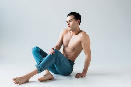 handsome man posing while sitting in blue jeans on white