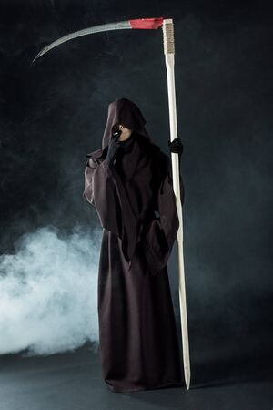Full length view of woman in death costume holding scythe and smoking cigarette on black background
