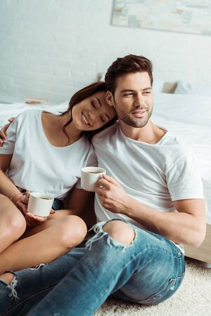 handsome man and cheerful woman holding cups in bedroom