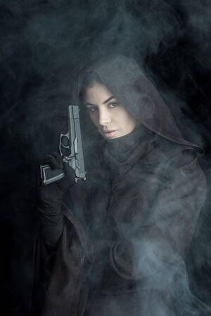 Woman in death costume holding gun and looking at camera on black background Imagens