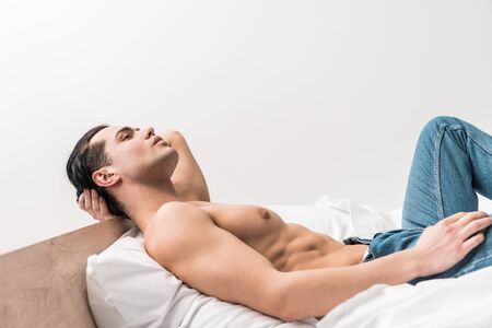 handsome shirtless man in blue jeans lying on bed at home
