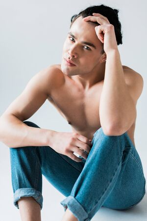 muscular and shirtless man sitting in blue jeans on white