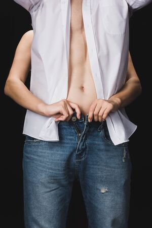 partial view of woman undressing boyfriend in blue jeans isolated on black
