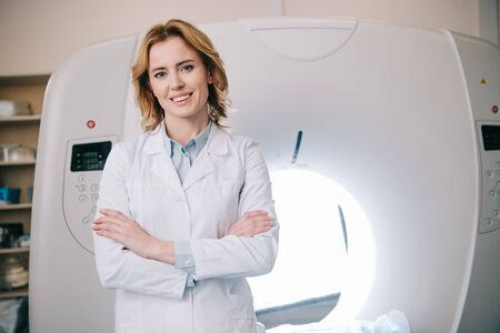 Radiólogo alegre de pie con los brazos cruzados cerca del escáner de tomografía computarizada y mirando a la cámara