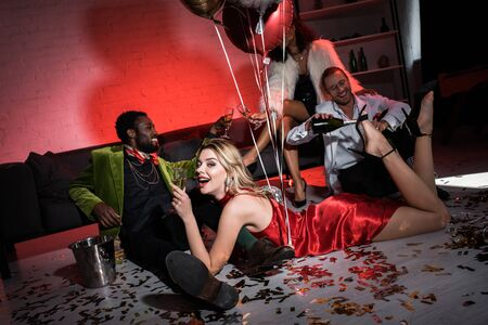 happy girl holding balloons while lying on floor near multicultural friends