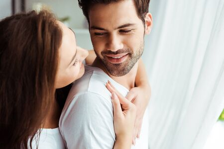 attractive girl hugging happy man standing in white t-shirt at home