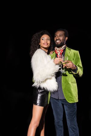 cheerful african american girl and handsome african american man holding champagne glasses isolated on black