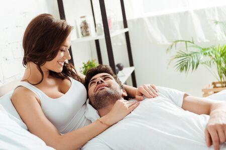 happy girlfriend looking at boyfriend lying on bed Reklamní fotografie