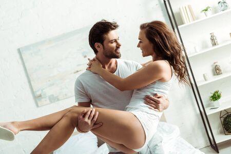 handsome man holding in arms beautiful girlfriend in bedroom Reklamní fotografie