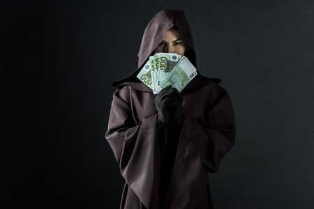 Front view of woman in death costume holding euro banknotes isolated on black background Banco de Imagens