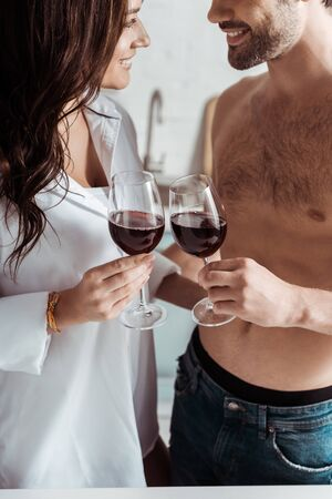 cropped view of cheerful muscular man holding wine glass near attractive girl at home