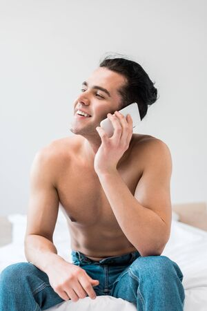 cheerful shirtless man sitting on bed and talking on smartphone at home