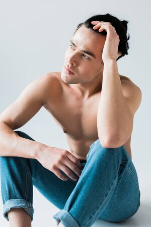 pensive and shirtless man sitting in blue jeans on white