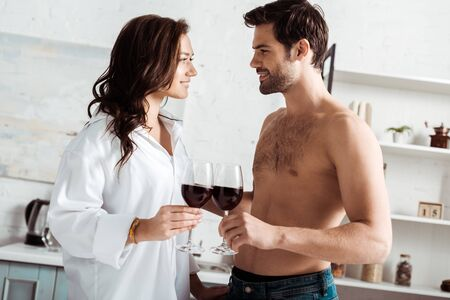 happy muscular man and happy girl clinking wine glasses at home Reklamní fotografie