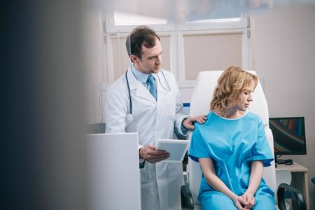 selective focus of doctor holding digital tablet and touching shoulder of upset woman