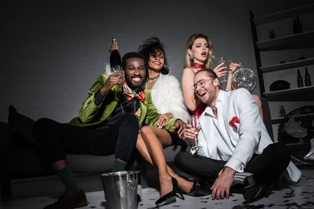 low angle view of african american man holding champagne glass while sitting near multicultural friends