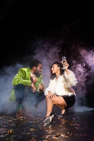african american man and woman holding champagne glasses while looking at each other near confetti on black with smoke