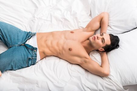 overhead view of confident man in blue jeans lying on bed at home Banco de Imagens