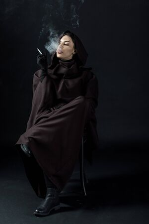 Pensive woman in death costume sitting on chair and smoking cigarette on black background Imagens - 125074642