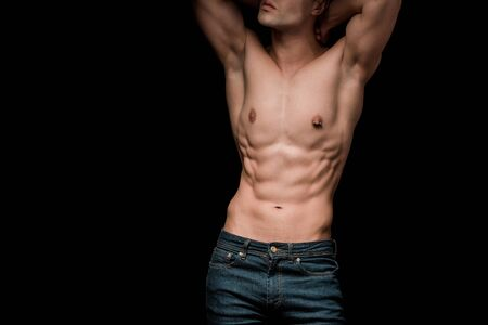 Cropped view of muscular young man standing isolated on black background
