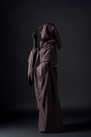 Side view of woman in death costume on black background Banco de Imagens