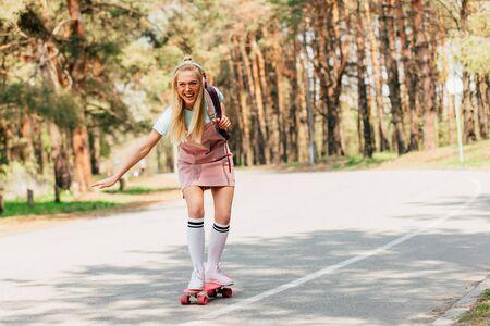 full length view of excited blonde girl skateboarding and listening music in headphones