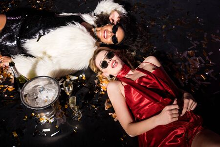 overhead view of blonde girl lying on floor with confetti near african american friend in sunglasses on black