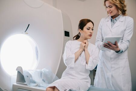 Smiling radiographer showing digital tablet with x-ray diagnosis to happy woman