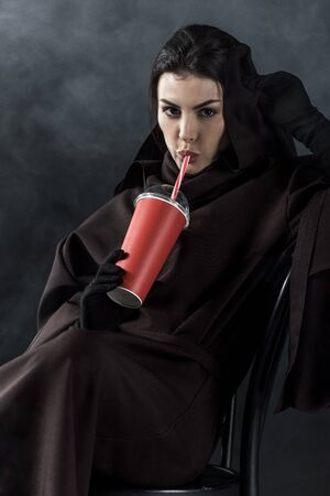 Woman in death costume sitting on chair and drinking beverage on black background Imagens