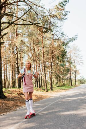 full length view of blonde girl in knee socks skateboarding on road Reklamní fotografie