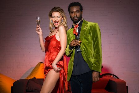 low angle view of excited blonde girl holding champagne glass near african american man
