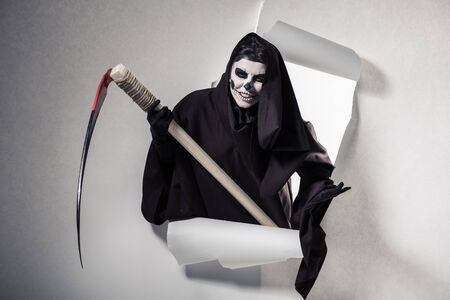woman in death costume holding scythe and getting out of hole in paper