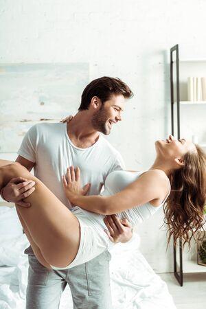 happy boyfriend holding in arms beautiful girlfriend in bedroom Reklamní fotografie