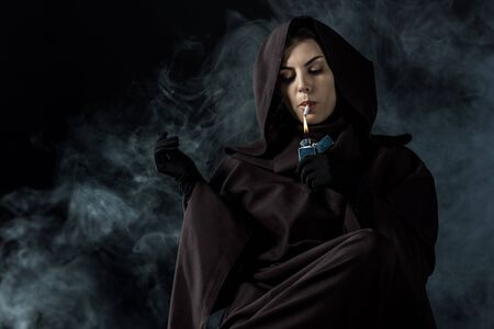 Woman in death costume lighting cigarette on black background Imagens