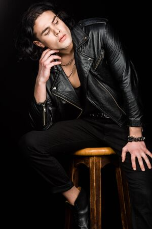 Pensive man in leather jacket sitting on chair isolated on black background Фото со стока