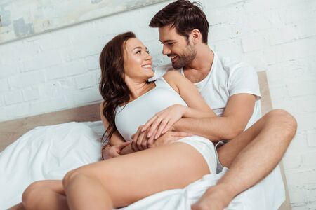 handsome man lying on bed with cheerful girlfriend in bedroom Reklamní fotografie
