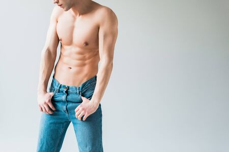 cropped view of muscular and shirtless man in jeans standing on white